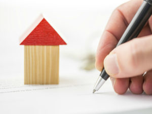 mano che firma contratto di affitto e una piccola casa in miniatura