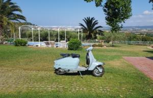residence per le vacanze con piscina e prato con una lambretta parcheggiata